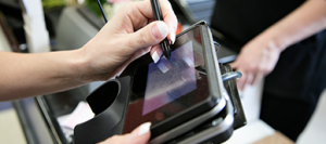 Woman using a Point of Sale machine for a Debit Card Purchase