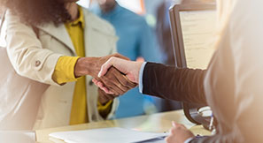 Two people shaking hands during a business transaction